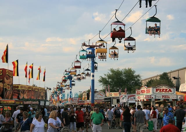 Visitors enjoying the Ohio State Fair while the Skyglider operates above.