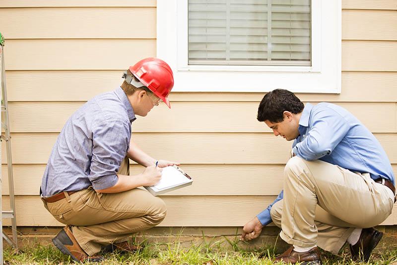 Home inspector assesses foundation.